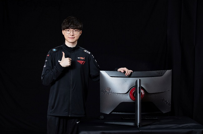 This image, provided by Samsung Electronics Co. on Sept. 22, 2020, shows T1's League of Legends esports player Lee Sang-hyeok, better known as Faker, posing for a photo with Samsung's Odyssey G7 Faker Edition curved monitor.