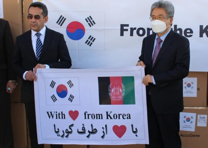 Rhee Zha-hyoung (R), South Korean ambassador to Afghanistan, and Ahmad Jawad Osmani, acting Afghan health minister, pose at a handoff ceremony held at Hamid Karzai International Airport in Kabul on Sept. 19, 2020, for some 40,000 COVID-19 test kits the South Korean government donated to Afghanistan. This photo was provided by the South Korean embassy in the country.