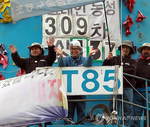 Kim Jin-suk (2nd from L) claps with other unionized workers on a 35-meter-high crane shortly before the completion of her 309-day strike on Nov. 10, 2011. (Yonhap)