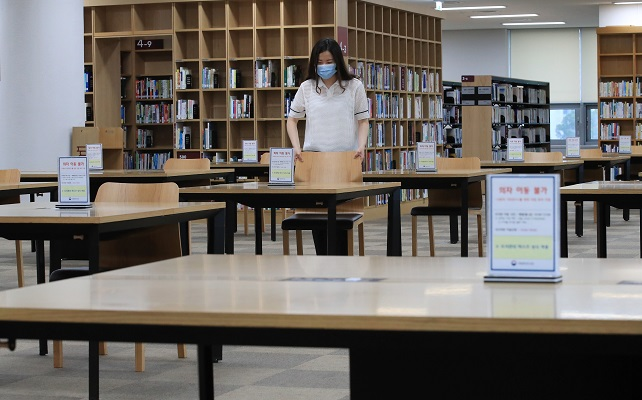 This file photo shows a staffer arranging seats for social distancing at the National Library of Korea in Seoul on July 20, 2020. (Yonhap)