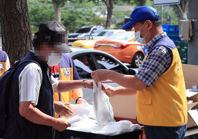 Volunteer workers hand out free protective masks and lunch boxes to elderly citizens in central Seoul on July 21, 2020. (Yonhap)