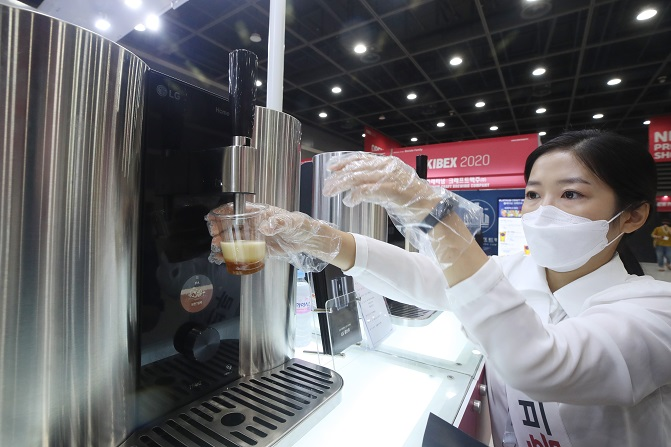 This photo taken on July 30, 2020, shows an official using LG Electronics Inc.'s homebrewing machine at the Korea International Beer Expo in Seoul.