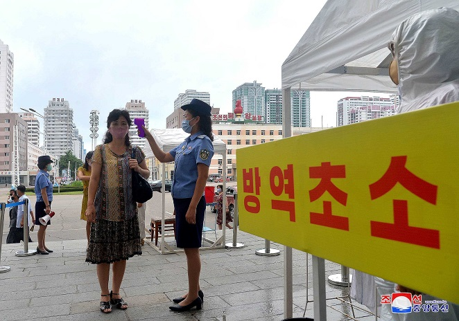 This photo, released by the North's Korean Central News Agency on Aug. 29, 2020, shows an official taking a citizen's temperature at Pyongyang Station in the capital to prevent the outbreak of the coronavirus.