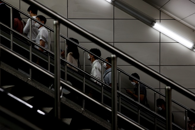 People wearing face masks ride an escalator at a subway station in Seoul on Sept. 1, 2020, amid the continued spread of the novel coronavirus. (Yonhap)