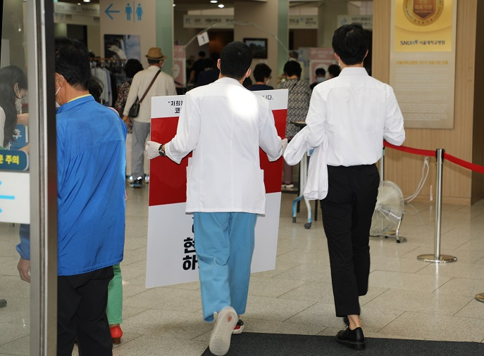 Trainee doctors at Seoul National University Hospital, who earlier held up signs to protest the government's medical reform plan, reenters the hospital after the KMA and parliament reached an agreement. (Yonhap)
