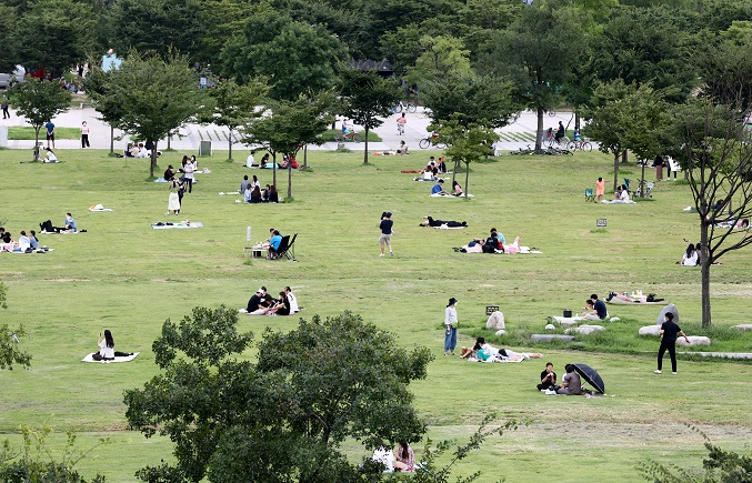 This photo shows people relaxing at Yeouido Han River Park in Seoul on Sept. 6, 2020. (Yonhap)