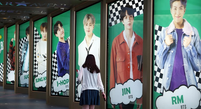 "A visitor walks past advertising signage showing K-pop septet BTS at a department store in Seoul on Sept. 9, 2020. The band's song ""Dynamite"" secured the No. 1 spot on Billboard's main singles chart for the second week in a row the previous day. (Yonhap)"