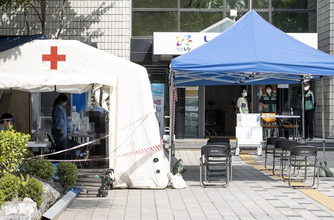 A visitor consults with a medical worker at a COVID-19 testing station at a community health center in Seoul on Sept. 14, 2020, when the number of new cases stood at 109, including 11 entrants from abroad, marking the 12th consecutive day the figure had stayed in the 100 level. (Yonhap)
