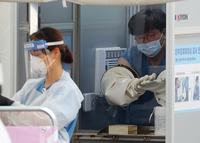 A health worker cleans his gloved hands with sanitizer after collecting a sample for a new coronavirus test at a test center in Seoul. (Yonhap)