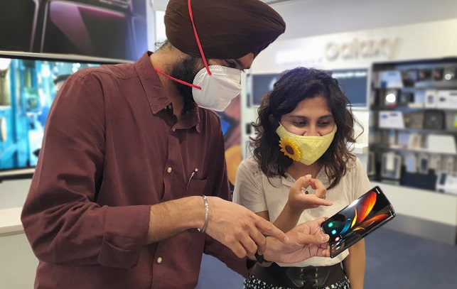 This photo, provided by Samsung Electronics Co. on Sept. 18, 2020, shows Indian consumers looking at the company's Galaxy Z Fold 2 smartphone at a store in Gurugram, India.