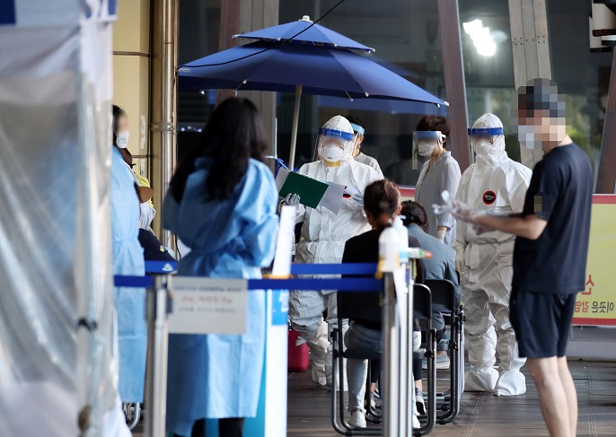 Citizens line up to receive new coronavirus tests at a testing center in Seoul's southeastern ward of Songpa on Sept. 18, 2020. (Yonhap)
