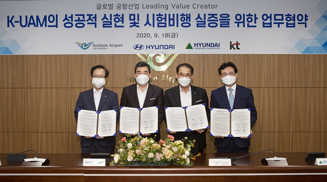 Officials from KT Corp., Hyundai Motor Co., Incheon International Airport Corp. and Hyundai Engineering & Construction Co. pose for a picture after signing an agreement to develop an urban air mobility service on Sept. 9, 2020, in this photo provided by the automaker.