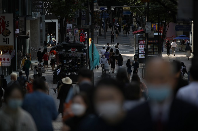 Pedestrians wearing protective masks walk around central Seoul on Sept. 20, 2020. (Yonhap)