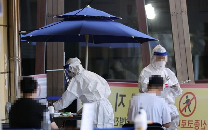 People fill in health questionnaires at an outdoor clinic in Seoul's Songpa Ward on Sept. 24, 2020, before undergoing polymerase chain reaction tests amid fears of a new coronavirus resurgence. (Yonhap)