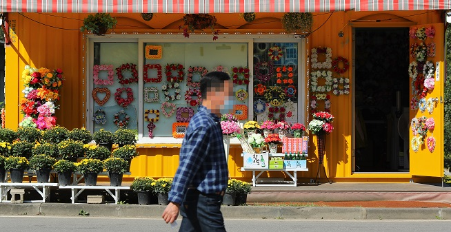 A man passes by a flower shop near a graveyard in Paju, just north of Seoul, on Sept. 27, 2020, with the number of visitors to their ancestral graves sharply down this year compared with a year earlier amid the COVID-19 pandemic. (Yonhap)