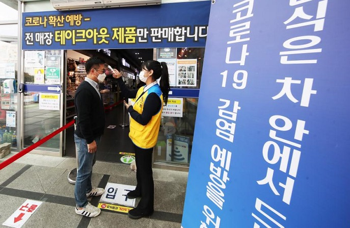 Workers take the temperature of visitors at a restaurant at a rest station on the Seoul-Busan Expressway in Giheung, south of Seoul, on Sept. 29, 2020, ahead of the Chuseok holiday on Oct. 1. People cannot dine at any highway restaurants from Sept. 29-Oct. 4, with only takeout available to prevent the spread of COVID-19. (Yonhap)