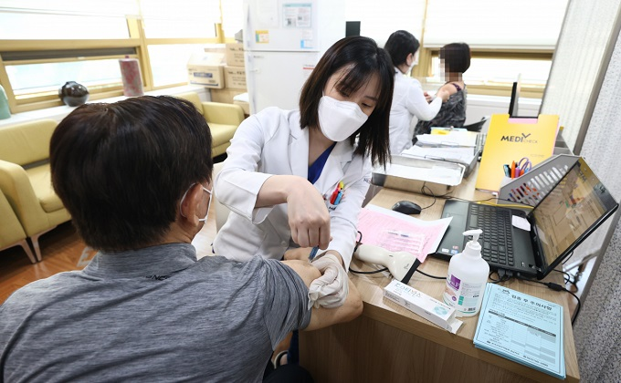 A man gets a flu shot at a building of the Korea Association of Health Promotion in Seoul on Oct. 19, 2020. (Yonhap)