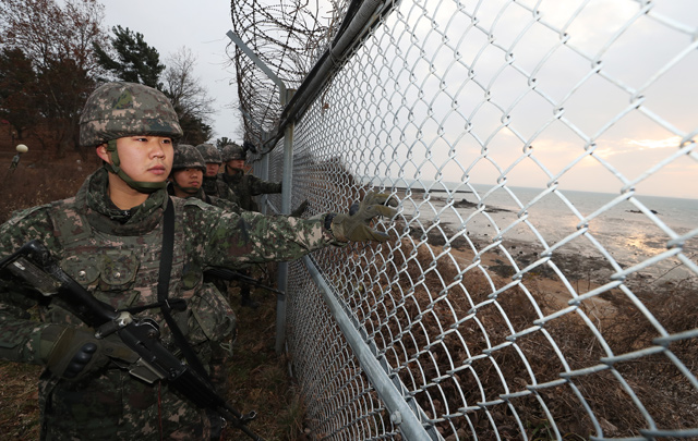 Troops belonging to the Army's 51st division check a fence at Gungpyeong Port, 55 kilometers south of Seoul, along the west coast of South Korea, on Dec. 30, 2019. (Yonhap)