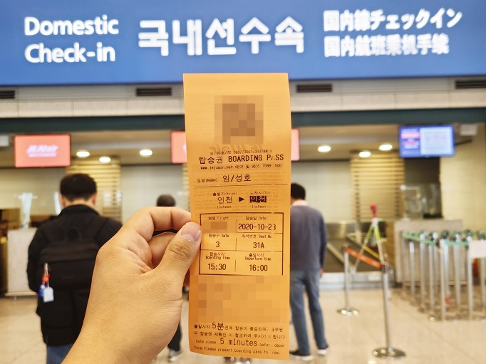 A customer holds up a Jeju Air Co.'s boarding ticket at Incheon International Airport, west of Seoul, on Oct. 23, 2020, for a special one-hour flight that departs from Incheon and returns to the airport as the carrier strives to survive the coronavirus crisis. (Yonhap)