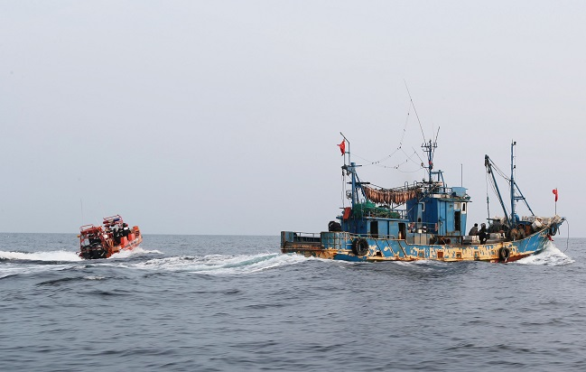 A Coast Guard motor boat (L) approaches a Chinese fishing boat operating without permission in South Korea's exclusive economic zone on Oct. 25, 2019.