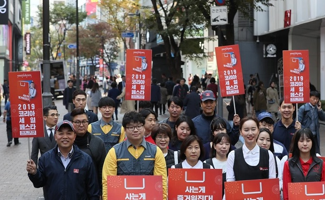 Corporate employees promote the 2019 Korea Sale FESTA in Myeongdong, a shopping mecca in downtown Seoul, on Oct. 31, 2019. (Yonhap)