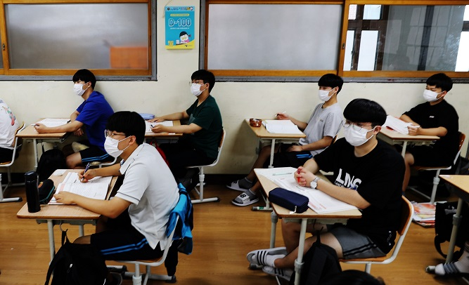 High school seniors wearing masks attend class in this undated file photo. (Yonhap)