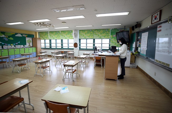 A teacher at an elementary school in central Seoul prepares for soon-to-be resumed offline classes on Oct. 16, 2020, as the education ministry eased attendance caps for schools amid relaxed virus curbs. (Yonhap)
