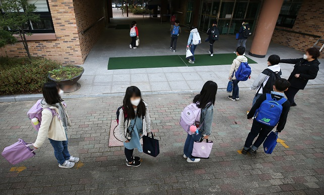 Students line up while keeping safe distances to enter their school in Suwon, south of Seoul, on Oct. 19, 2020. (Yonhap)