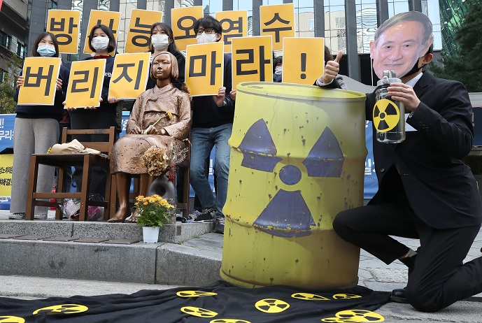 A protestor wearing a mask depicting Japanese Prime Minister Yoshihide Suga simulates the disposal of radioactive water into the ocean during a rally in Seoul on Oct. 19, 2020, to oppose the release of water containing radioactive materials stored at the Fukushima nuclear power plant in Japan. (Yonhap)