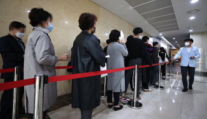 Citizens wait in line to receive a free flu shot at a medical center in Seoul on Oct. 19, 2020. (Yonhap)