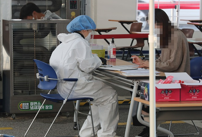 A medical worker carries out new coronavirus tests at a makeshift clinic in southern Seoul on Oct. 20, 2020. (Yonhap)