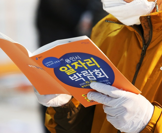 A job seeker wearing a protective mask and gloves reads a pamphlet at a job fair held in Yongin, south of Seoul, on Oct. 21, 2020. (Yonhap)