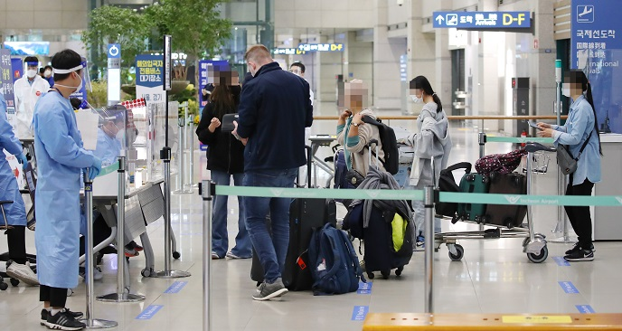 International arrivals show their passports to officials wearing protective gear at Incheon International Airport, South Korea's main gateway west of Seoul, on Oct. 22, 2020. (Yonhap)