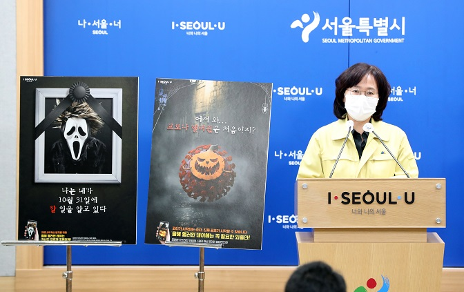 """A poster, which says, """"I know what you did on Oct. 31,"""" is displayed next to Park Yoo-mi, a senior official responsible for public health at the Seoul metropolitan government, as she holds a press conference at City Hall in Seoul on Oct. 28, 2020, telling people to refrain from gathering during the upcoming Halloween on Oct. 31 amid the coronavirus pandemic. (Yonhap)"""