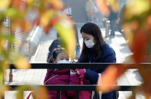 A mother helps her daughter wear her backpack in front of an elementary school in Goyang, Gyeonggi Province, on Oct. 19, 2020. (Yonhap)