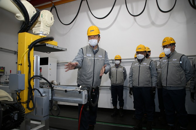 Officials from Daewoo Shipbuilding & Marine Engineering Co. look at an AI-based welding quality monitoring robot in Okpo, Geoje Island, about 400 kilometers south of Seoul, in this photo provided by the shipbuilder on Nov. 24, 2020.
