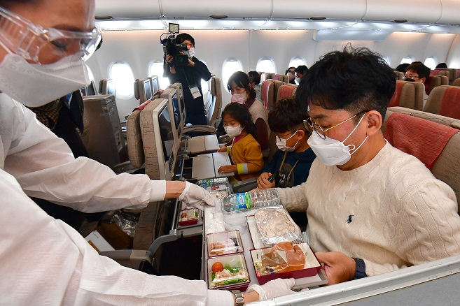 This photo, provided by the Incheon International Airport press pool, shows a flight attendant serving an in-flight meal on an Asiana Airlines flight to nowhere on Oct. 24, 2020.