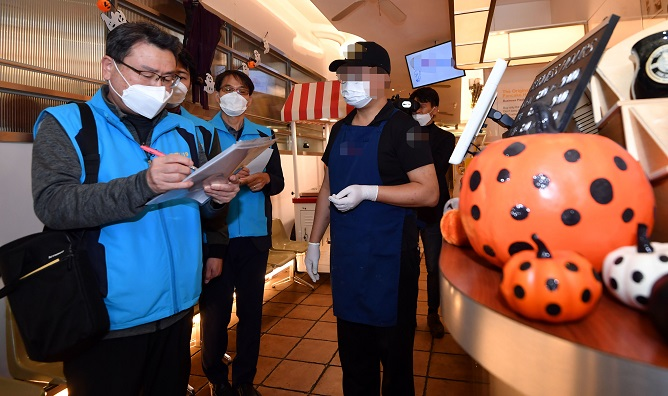 Seoul city officials monitor a visitor check-in system at a restaurant in Itaewon in Seoul on Oct. 29, 2020, ahead of Halloween, on concerns over the spread of COVID-19. (Yonhap)