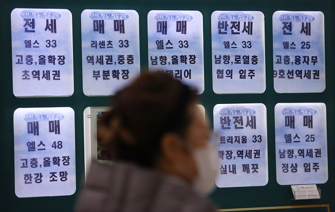 This photo, taken on Nov. 18, 2020, shows a citizen walking past a real estate office with the sale and rental prices of apartments in Songpa, eastern Seoul. (Yonhap)