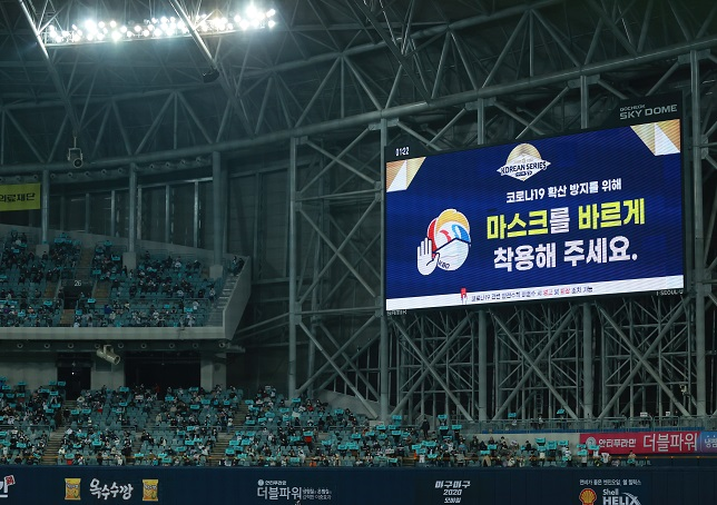 A message displayed on one of the two scoreboards at Gocheok Sky Dome in Seoul on Nov. 18, 2020, reminds spectators to wear masks properly during Game 2 of the Korean Series between the Doosan Bears and the NC Dinos. (Yonhap)