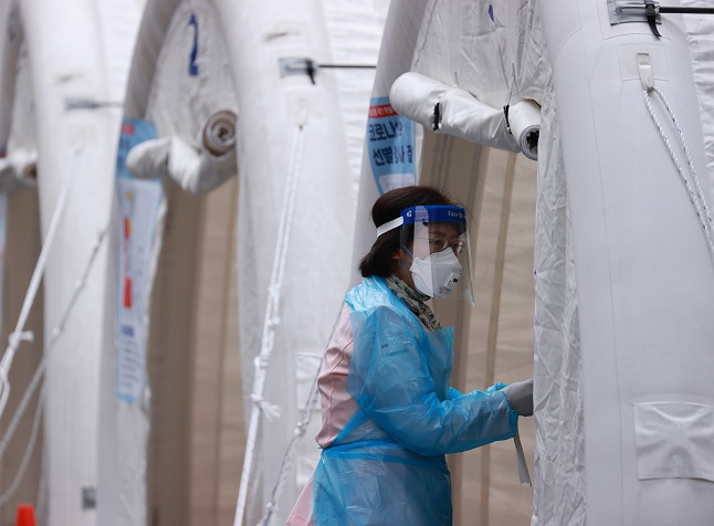 A health worker clad in protective gear prepares to work at a makeshift virus test clinic in Seoul on Nov. 20, 2020. (Yonhap)