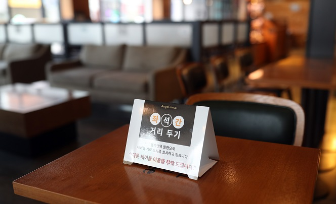 A coffee shop in Hadong, South Gyeongsang Province, puts up a sign on keeping a distance between tables after the county enforced Level 2 social distancing on Nov. 22, 2020. (Yonhap)