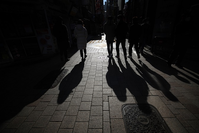 People walk on a street in Myeongdong, a shopping district in downtown Seoul, on Nov. 23, 2020. (Yonhap)