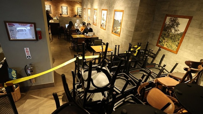 Chairs and tables are moved to a corner at a cafe in Seoul on Nov. 23, 2020, as toughened social distancing rules are to only allow takeout and delivery sales at the place. (Yonhap)