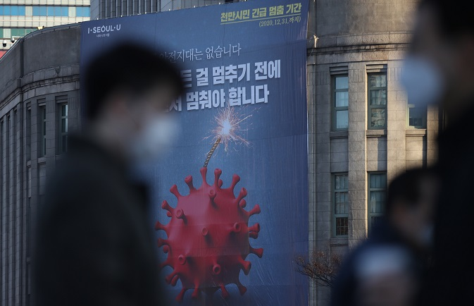 This Nov. 25, 2020, photo shows a massive banner emphasizing the enhanced social distancing campaign hanging on Seoul Metropolitan Library in central Seoul. (Yonhap)