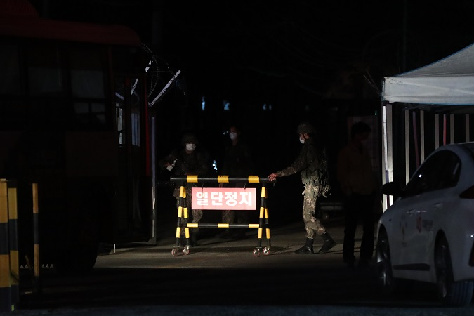 Soldiers open the front gate of an Army boot camp in the northern county of Yeoncheon on Nov. 25, 2020, to allow the entry of health authorities after dozens of newly enlisted soldiers tested positive for the new coronavirus. (Yonhap)
