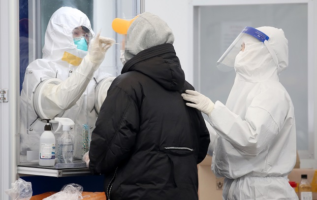 Health workers clad in protective gear carry out a COVID-19 test on a citizen at a makeshift virus testing clinic in Seoul on Nov. 26, 2020. (Yonhap)