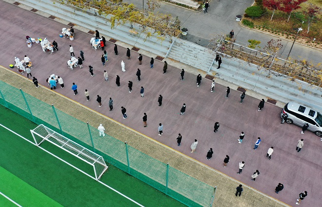 Students keep a distance from one another while waiting in line to receive COVID-19 tests at a makeshift virus testing clinic at a middle school in Gwangju on Nov. 26, 2020. (Yonhap)