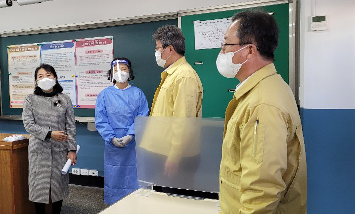 Acting Busan Mayor Byun Seong-wan (2nd from R) inspects a proctor's quarantine outfit (2nd from L) and a test room that test takers with fever will use during an inspection of a high school in Busan on Nov. 30, 2020, three days ahead of the country's college entrance examination. (Yonhap)