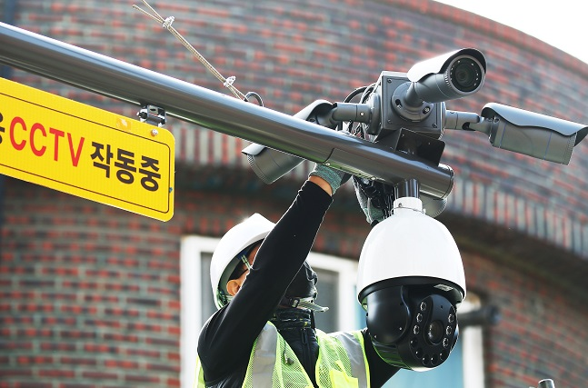 In this file photo taken on Oct. 13, 2020, an official sets up a surveillance camera in a village in Ansan, Gyeonggi Province. (Yonhap)